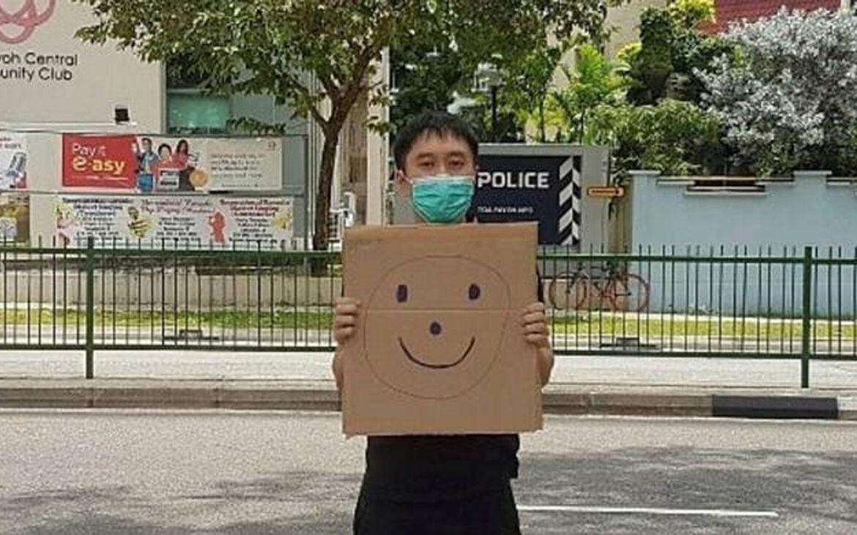 """""""Jolovan Whom"""" ชายชาวสิงคโปร์ถูกจับเพราะยืนถือสัญลักษณ์ใบหน้ายิ้มอยู่หน้าสถานีตำรวจ"""